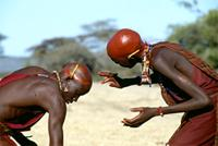 Maasai warriors applying red ochre to shaved heads, Kenya