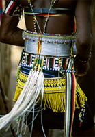 A Dancer wearing finely crafted aluminium belts and beaded girdles, Senegal