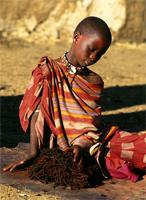 A Maasai warrior's young girlfriend caresses his fallen locks, Kenya