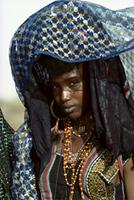 A young Woodabe woman shielding her glance under a veil, Niger
