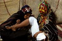 Berber mother tenderly kisses the girl's limbs before massaging them with henna, Morocco