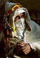 The groom, traditionally dressed for marriage, wears two wedding robes and a silk veil over his nose and mouth, Morocco
