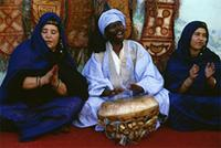 A Hassania drummist and women clapping and ululating to the mesmerizing beat during the Guerda dance, Mauritania