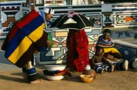 Concealed under her umbrella, a Ndebele bride receives gifts on her wedding day, South Africa