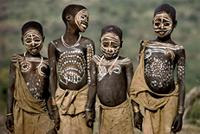 Surma children from Ethiopia decorate their bodies using chalk and earth pigments, Ethiopia