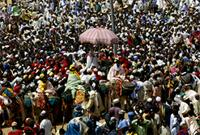 Shaded by the pink umbrella, the Emir of the Hausa city-state Katsina leaves his palace to greet the populace on the first morning of the Sallah celebrations. Nigeria