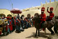The Emir of Katsina, under the umbrella, returns to his palace along with his entourage and two of his sons on horseback. Sallah celebrations, Hausa, Katsina, Nigeria
