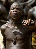 A Sana initiate testing the sharpness of his chosen knife against his neck, Benin