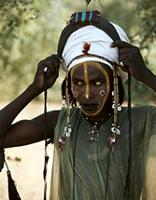 A young Wodaabe man dressing up for the annual Geerewol festival, Sahara