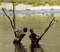 Borana men digging up black mud from Chew Bet crater lake, Ethiopia