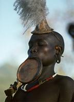 A Surma relative of deceased wears a clay lip plate during burial, Ethiopia
