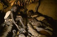 Surma family resting by fire, Ethiopia