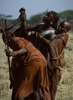 Emotionally-crazed Maasai warrior being carried by mothers.