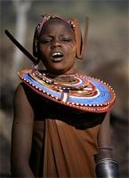 Young Maasai woman adorned with earrings and necklace.