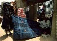 Woodabe women buy dark-blue hand-woven fabric to fashion into wrappers, Niger.