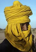 Man wrapped against wind and sand in long yellow turban, Woodabe people of Niger.