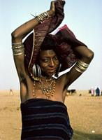 Woodabe woman tieing a turban, wearing elaborate earrings and arm bands.