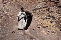 A nun emerging from tunnel leading to rock-hewn church.