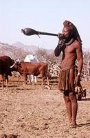 Himba man blowing traditional trumpet.