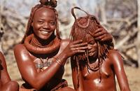 Young Himba woman beautified with ochre and butterfat, playing with sister.