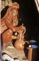 Himba woman with milk gourd and containers.