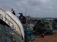 Photograph of people and a fishing net opposite from the Castle, Elmina, Ghana