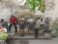 Photograph of people sitting on a well, Lamu Town, Kenya
