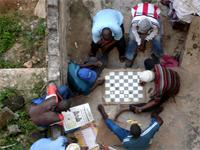 Photograph of people playing chess in a corner from the Fort, Lamu, Kenya