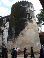 Photograph of one tower of the Lamu Fort and some people, Kenya
