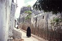 Veiled woman walking up a street next to Lamu Fort.