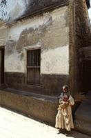 A young girl standing outised an old Lamu building.