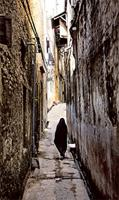 A veiled woman makes her way along a narrow street to Mkomani.