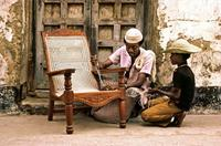 Swahili craftsmen string a locally made chair.