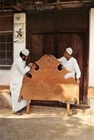 Craftsmen working on a Swahili bed with carved headboards and night tables, usually designed for brides.