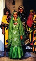 A Swahili bride dressed in green standing in front of three female relatives.