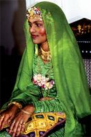 A Swahili bride dressed in green, and wearing golden bracelets and rings.