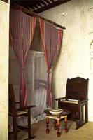 A bed at the inner room of a Swahili home with curtains suspended from lacquered poles.