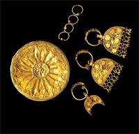 Round gold earlobe disk, crescent-shaped gold filigree earrings, and fine, gold rings.