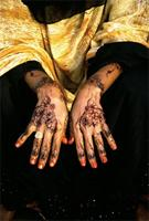 A Swahili girl displays her hands that have been decorated with a dye made of powdered henna, water and the juice of unripe limes.