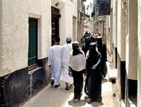 A main street in lamu with veiled women and robed men.