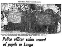 Police officer calms crowd of pupils in Langa